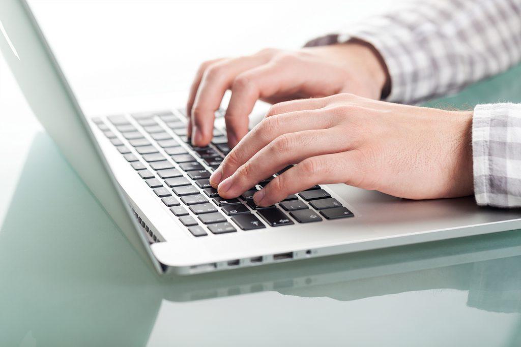 Osoba pisze na laptopie